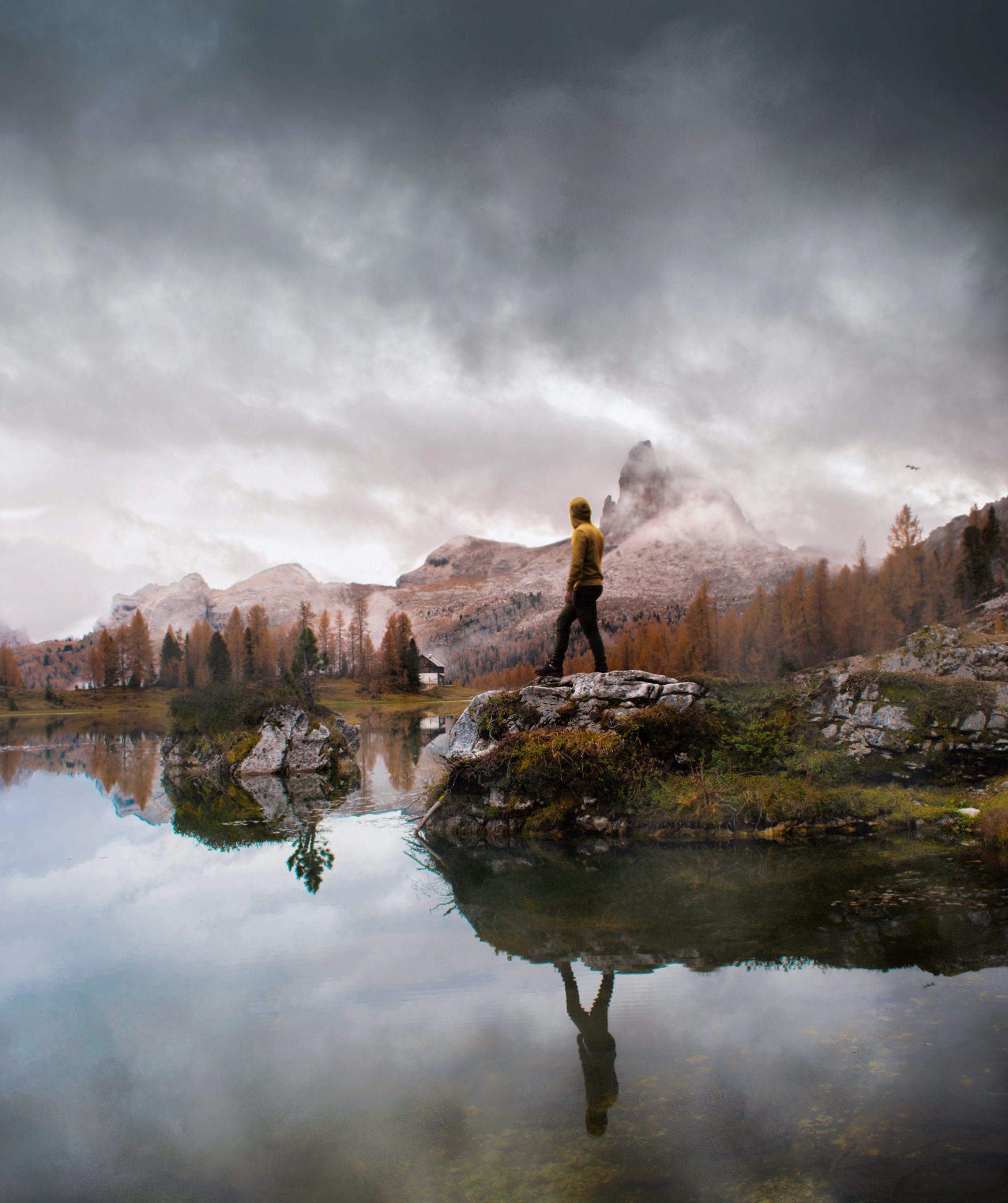 persona su roccia in mezzo al lago